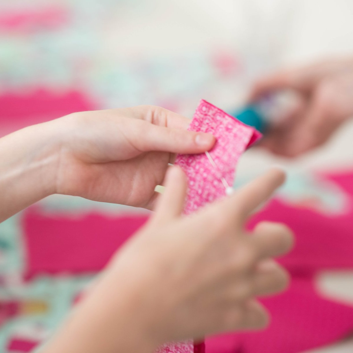 Closeup of hands pinning fabric